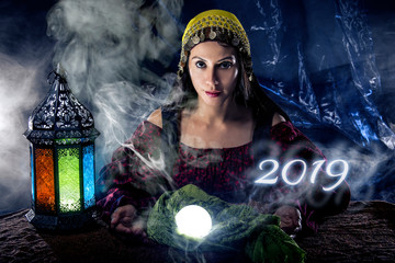 Female fortune teller or psychic reading with a cystal ball predicting the future of the year 2019