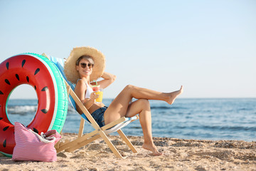 Young woman with cocktail in beach chair at seacoast
