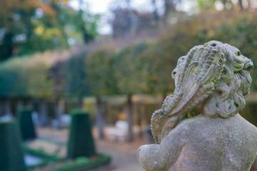 Stone angel statue in garden. Guardian angel statue in sunlight as a symbol of love in garden.