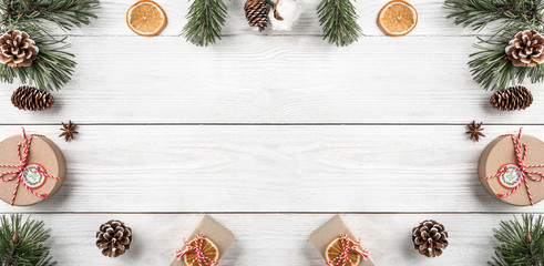 Christmas gift boxes on white wooden background with Fir branches, pine cones. Xmas and Happy New Year theme. Flat lay, top view, wide composition