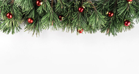 Christmas Fir branches with red decoration on white background. Xmas and Happy New Year theme. Flat lay, top view, wide composition