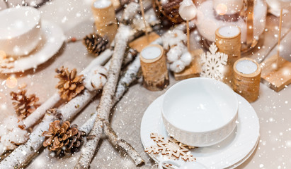 Christmas table place setting with christmas pine cones, wooden decorations, bokeh, snowflakes. Xmas and Happy New Year theme, selective focus
