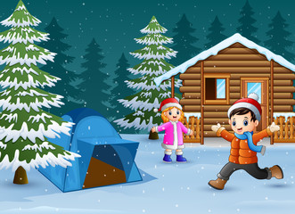 Happy kids play in front of a snowy wooden house