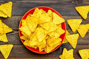 Mexican snack. Make nachos. Crispy nachos on plate on dark wooden background top view