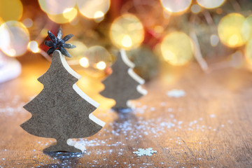 Two small wooden Christmas trees with festive light on background, horizontal composition