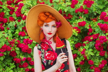 Vintage girl with red lips in dress with a print of roses with red candy on summer garden. Redhead model in summer hat on background of roses bush. Stylish vintage woman. Sweet candy. Red lollipop