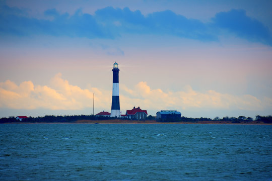Fire Island Lighthouse with beaming light with Long Island Sound, New York, in the foreground with a colorful sky with dark ominous clouds.