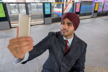 Indian businessman sitting at train station while taking selfie with mobile phone