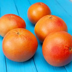 Ripe fresh grapefruits on a bright blue table