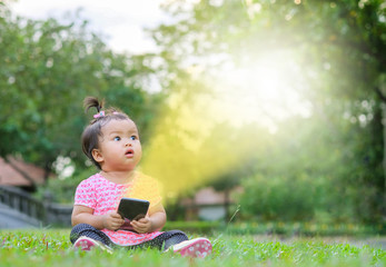 Closeup little girl sit on grass floor and look at space like a text box caused by light from mobile phone on park view background