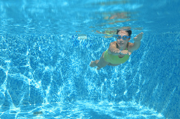 Beautiful young girl holding white blank board in swimming pool under water, fitness and fun on family vacation