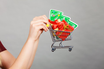 Woman hand holding cart with christmas tree