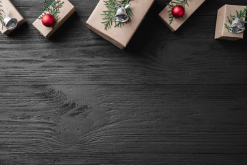 Christmas card with gifts on a dark wooden rustic background, place for text. Xmas and happy new year greeting card. Top view, flat lay.