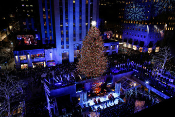 People watch the Christmas tree lighting at Rockefeller Center in the Manhattan borough of New York