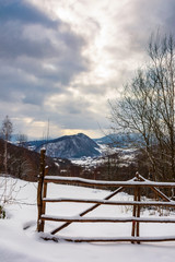 wooden fence on a snowy hill in mountains