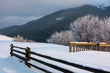 wooden fence on snowy hill in morning light
