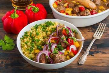 Beef and vegetables stew. White casserole and bowl with meat, bulgur, red onion and fresh parsley on wooden table