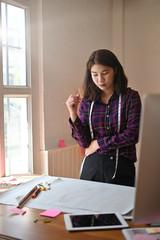 Female fashion designer working on workplace with design new fashion.