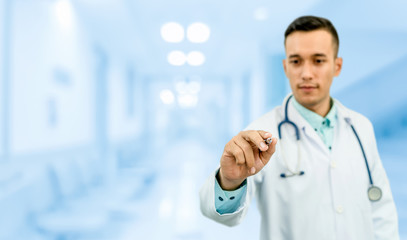Doctor pointing pen at empty copy space for your text. Healthcare and medical service.