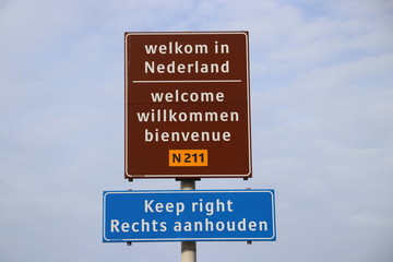 Welcome sign at Hoek van Holland for travelers from England with warning to keep right for driving lane.