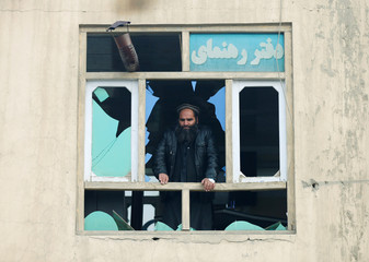 An Afghan man looks out the broken window at the site of a car bomb attack in Kabul