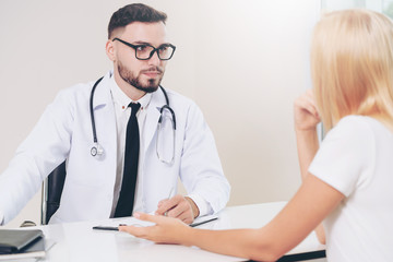 Male doctor is talking to female patient in hospital office. Healthcare and medical service.
