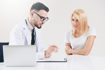 Male doctor talks to female patient in hospital office while writing on the patients health record on the table. Healthcare and medical service.