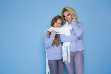Portrait of beautiful blond girls, mother with her daughter in winter clothing on the background.