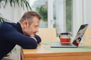 Bored man staring at his laptop computer