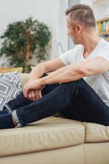 Unshaven man sitting on a sofa thinking