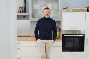 Relaxed confident man standing in his kitchen