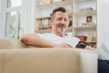 Middle-aged man sitting in a living room relaxing