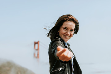 Happy woman doing the follow me hand by the Golden Gate Bridge, San Francisco