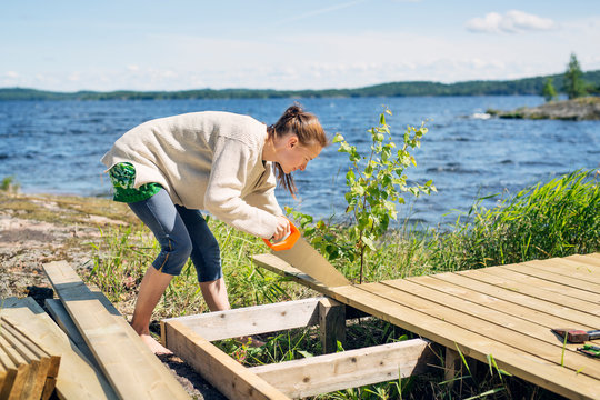 Mid adult woman building a deck in front of a lake in Finland