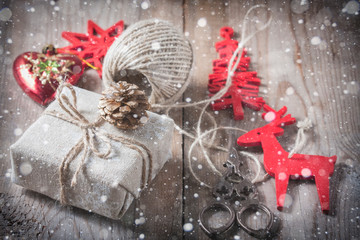 Gift box wrapped linen cloth and decorated with  cord, jute, christmas decoration on brown vintage wooden boards background. Drawn Snowfall