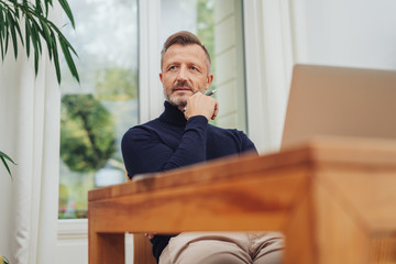 Thoughtful man seated at a wooden table