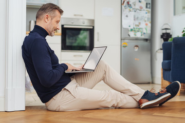 Man relaxing with a laptop on the parquet floor