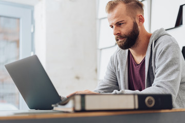 Man working on laptop in modern home office