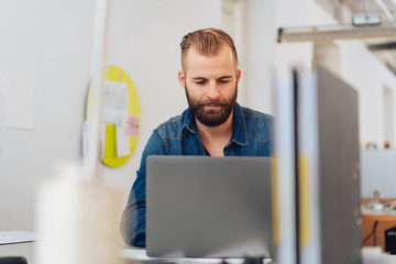 Young, urban man on laptop in modern office
