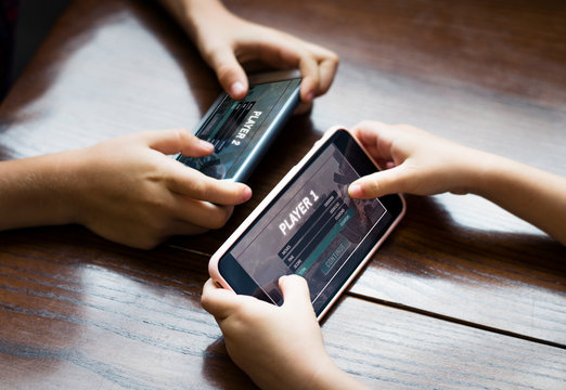 Little boy playing a mobile game against his sister