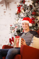 Image of happy man in Santa hat with gift in his hands