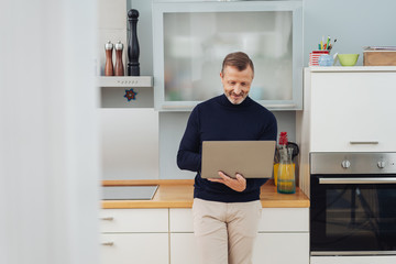 stylish man using a laptop computer in a kitchen