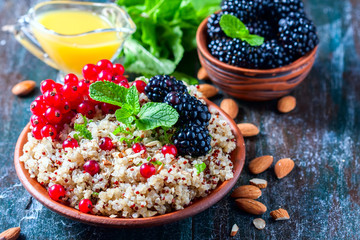 Quinoa salad with berries, mint and walnuts on a dark wooden background. Superfoods  clean eating concept.