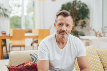 Middle age man in white t-shirt on the couch