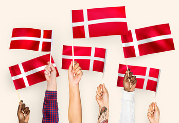 Hands waving the flags of Denmark