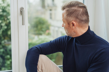 Man sitting staring through a window