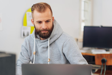Man in casual clothing working on laptop in office