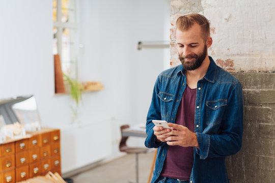 Modern, stylish man texting on phone at home