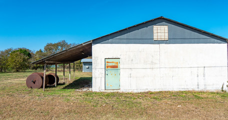 Rural building with colorful, rusty door in a grassy field, with overhang and rusty fluid tanks