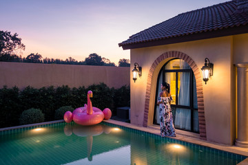 young woman in dress walking by the pool of luxury vila